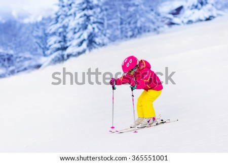 Child skiing in mountains. Active toddler kid with safety helmet, goggles and poles. Ski race for young children. Winter sport for family. Kids ski lesson in alpine school. Little skier racing in snow - stock photo