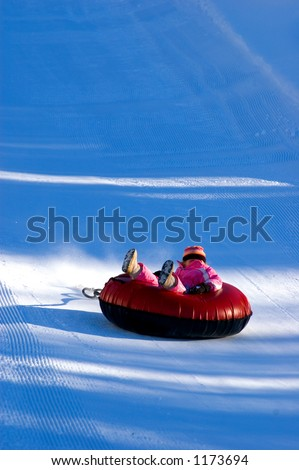 child sledding on inner tube - stock photo
