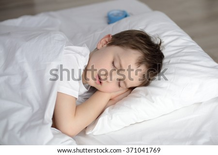 Child sleeping in bed, happy bedtime in white bedroom. Sleeping boy. Sleeping child - stock photo