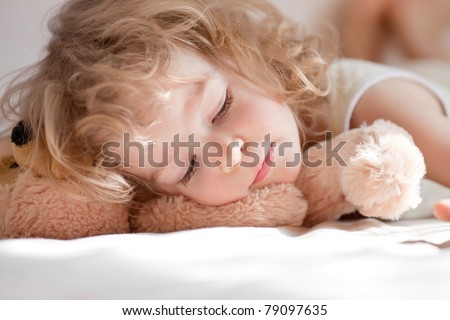 Child sleeping in bed with teddy - stock photo