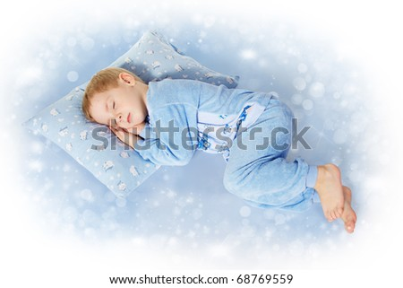 Child sleeping on pillow in sleepwear. Magic blue background - stock photo