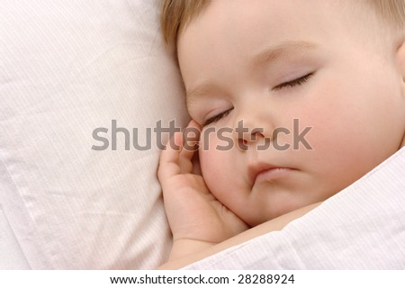 Child sleeping with hand under his cheek, high key portered - stock photo