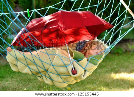 Child sleeps in a hammock in the garden.