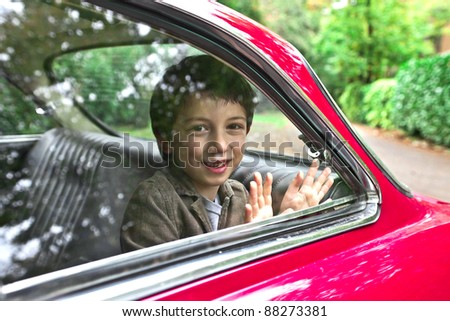 Child smiling from a car - stock photo