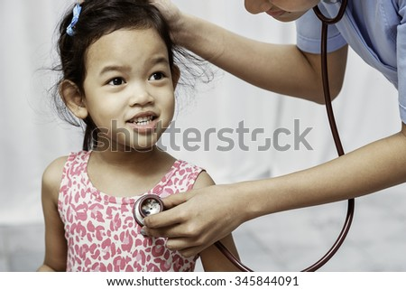 child smiling while the paediatrician listens to her heart beats
