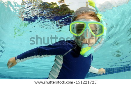 child snorkeling and swimming in pool with goggles
