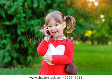child speaks on the phone in the park. - stock photo