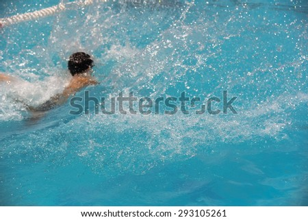 Child splashing in summer water pool