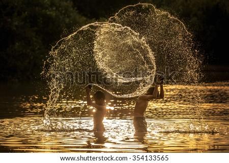 Child splashing played in pond at sunset - stock photo