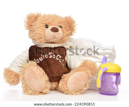 Child stack of diapers and baby feeding bottle with water and soft teddy bear toy on a white background - stock photo