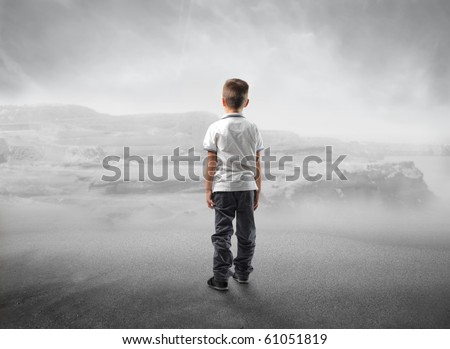 Child standing in front of a desert - stock photo