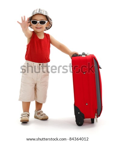Child standing near luggage, wearing hat and sunglasses, holding his luggage and waving good bye with hand - stock photo