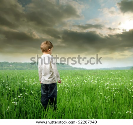 Child standing on a green lawn and observing the panorama - stock photo