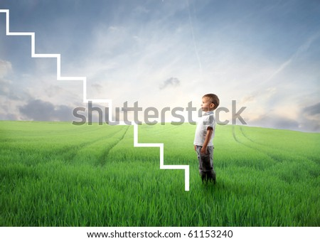 Child standing on a green meadow in front of a stairway - stock photo