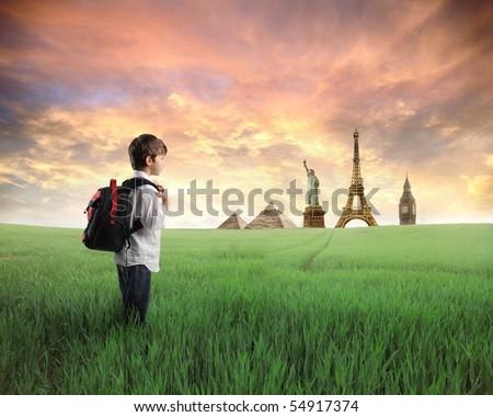 Child standing on a green meadow with landmarks from diverse cities on the background - stock photo