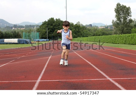 Child standing on a running track - stock photo