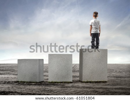 Child standing on the highest of three cubes on a field - stock photo