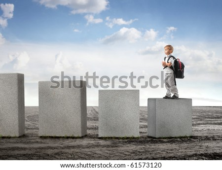Child standing on the lowest cube on a field - stock photo