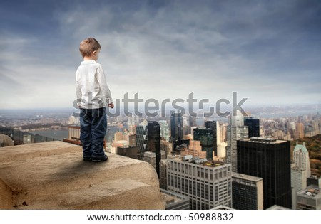 Child standing on the top of a skyscraper and observing the city below - stock photo