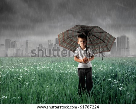 Child standing under an umbrella on a green meadow with stormy sky on the background - stock photo
