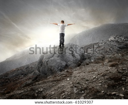 Child standing with open arms on a rock