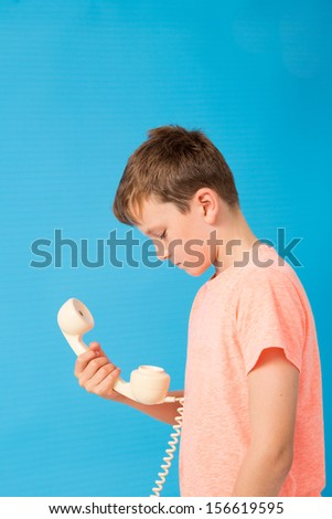 Child staring at a telephone - stock photo