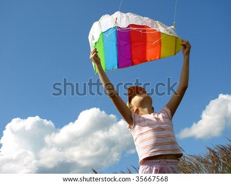 child starts flying kite against blue sky with clouds - stock photo