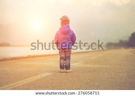 Child stay on the outdoors road - stock photo
