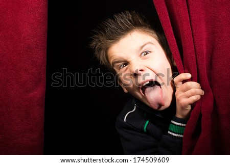 Child stick out his tongue.Appearing beneath the curtain - stock photo