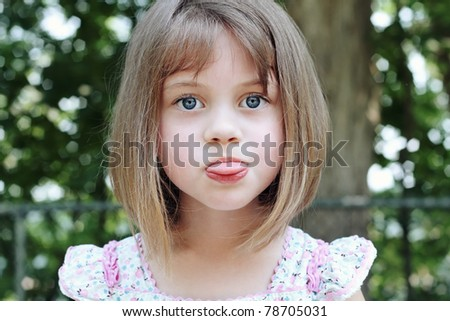 Child sticking out her tongue. - stock photo