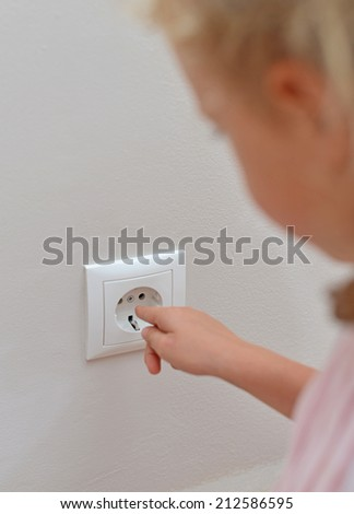 Child sticks his fingers in the socket. Dangerous situation at home. - stock photo