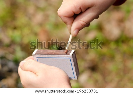 Child striking a safety match on a box of matches against a green grass background , close up of the hand - stock photo