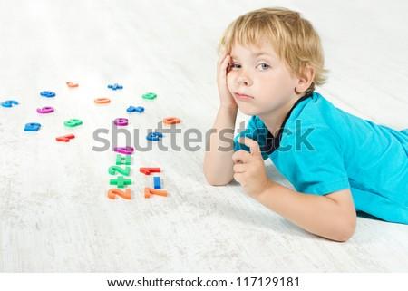 Child studying mathematics. Tired - stock photo