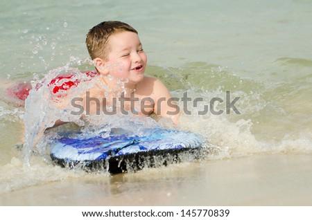 Child surfing on bodyboard at beach - stock photo