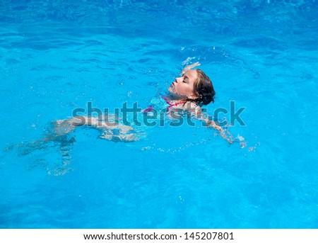 Child swimming backstroke in the swimming pool - stock photo