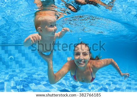 Child swimming lesson - baby with mother learning to dive underwater in pool. Healthy active family lifestyle, physical exercise, water sport activity with parent on summer holiday in fitness center