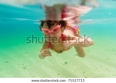 Child swimming underwater in sea. Active girl swims and having fun. Child sport on summer vacation - stock photo