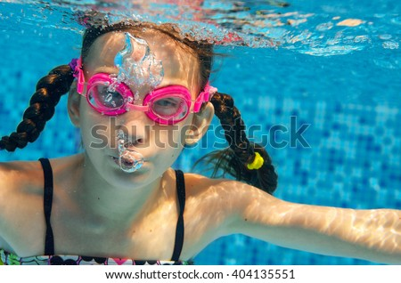 Child swims in pool underwater, funny happy girl in goggles has fun under water and makes bubbles, kid sport on family vacation  - stock photo