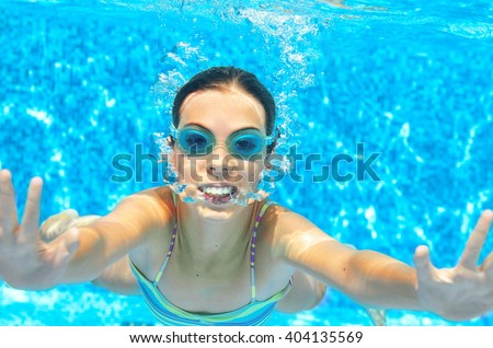 Child swims in pool underwater, funny happy girl in goggles has fun under water and makes bubbles, kid sport on family vacation
