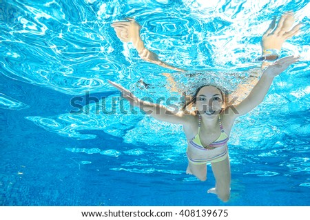Child swims in pool underwater, girl has fun under water, active kid sport on family vacation