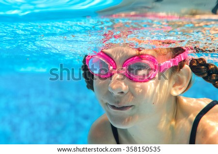 Child swims in pool underwater, happy active girl in goggles has fun in water, kid sport on family vacation  - stock photo