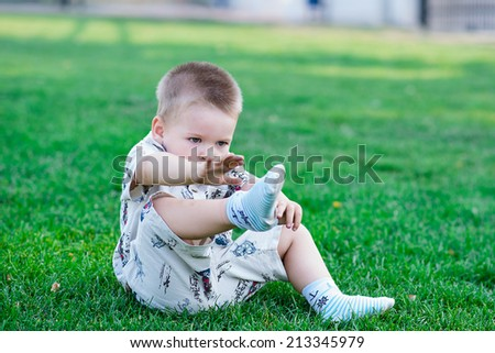 child takes sock with foot - stock photo