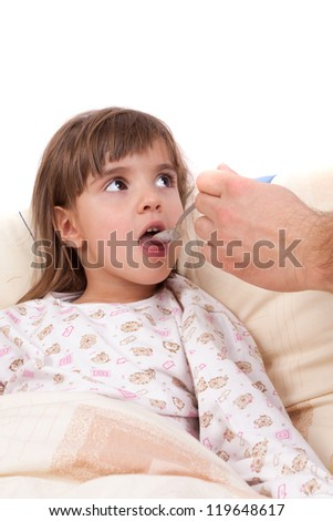 Child takes vitamins by spoon