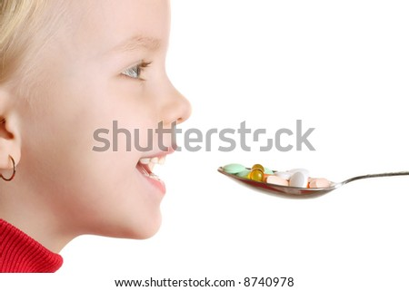 Child takes vitamins by spoon - stock photo