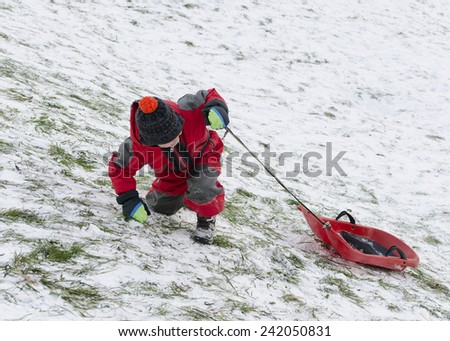 Child taking advantage of snow, pulling a sledge up a hill barely covered with snow.  - stock photo