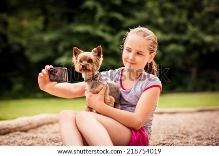Child taking photo of herself and her dog - outdoor in nature - stock photo