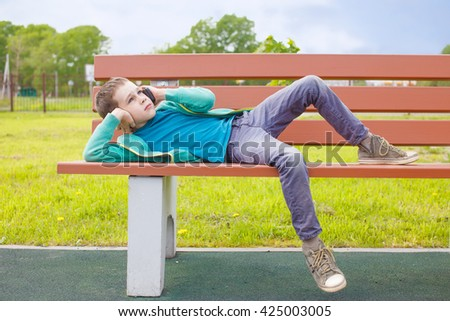 child talking on the phone while lying on a bench. bored boy waiting for the call is finished - stock photo