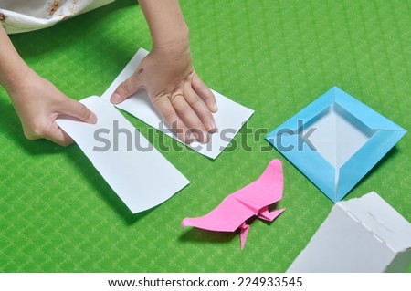 child tear paper to make origami paper craft - stock photo