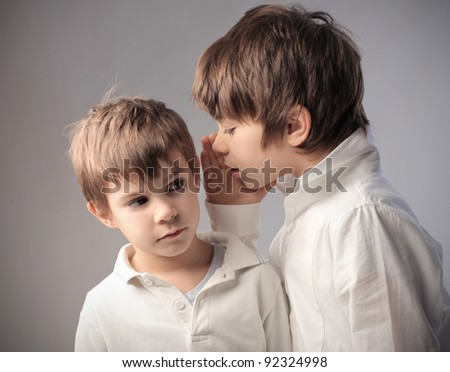 Child telling a secret to his brother - stock photo