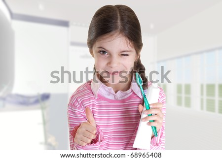 child thumb up with tooth paste and brush in the bathroom - stock photo